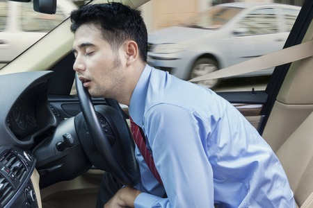 drives: Male entrepreneur sleeping in the car while driving on the road at traffic jam