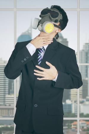 contaminacion del aire: Empresario de sexo masculino de pie en la oficina con una m�scara de gas y conseguir ataque al coraz�n