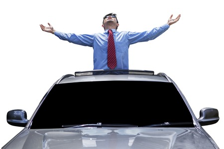 sunroof: Successful young businessman standing on the car and enjoy freedom through the sunroof