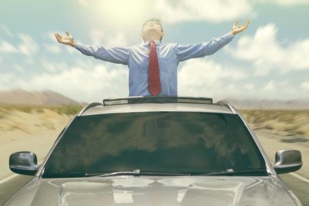 dream car: Joven empresario de pie en el techo del coche, mientras que gozan de libertad Foto de archivo
