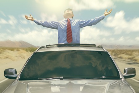 Young entrepreneur standing on the sunroof of the car while enjoy freedom