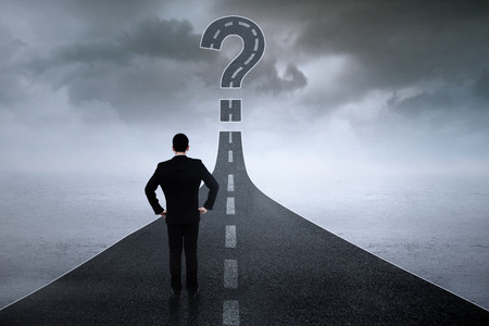 Back view of businessperson standing on the road while looking at question sign photo