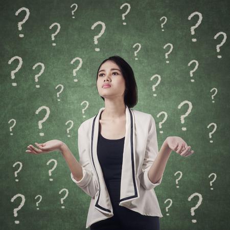 confundido: Empresaria joven que parece confundido con signos de interrogación en la pizarra