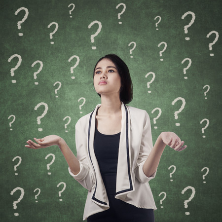 Young businesswoman looks confused with question marks on the blackboard Stock Photo