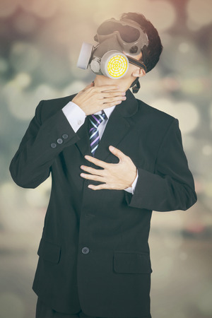 stifle: Businessman in formal suit and wearing gas mask, shot with bokeh background Stock Photo