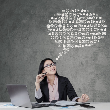 business idea: Young female entrepreneur working on the table with laptop and look at web icons Stock Photo