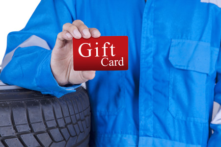 auto repair: Closeup of male mechanic with blue uniform standing near tires and showing a gift card Stock Photo