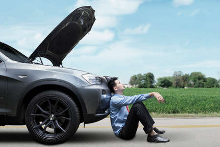 assist: Young businessman waiting a help while sitting on the road with broken car Stock Photo