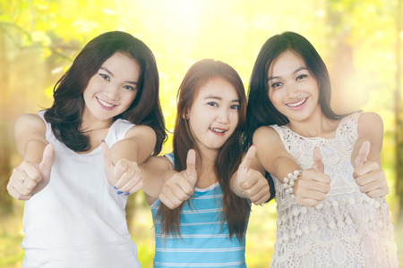 asian group: Portrait of three beautiful teenage girls enjoy summer holiday and showing thumbs up on the camera