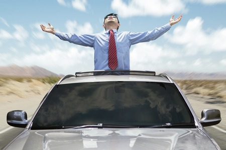 sunroof: Happy entrepreneur with new car, standing on the sunroof while enjoying freedom Stock Photo