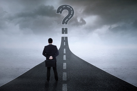 Young businessman standing on the highway while looking at a question symbol photo