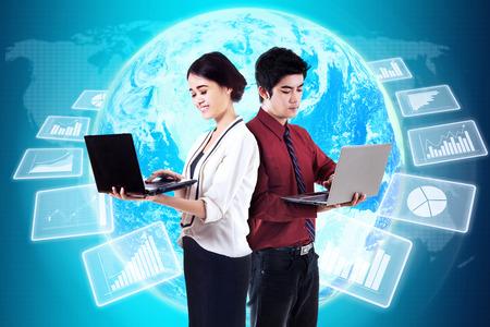 jovenes empresarios: Dos empresarios j�venes que trabajan con ordenador port�til frente a futuristas estad�sticas de las empresas globales Foto de archivo