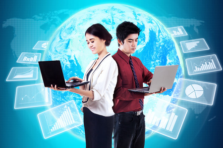 young entrepreneurs: Two young entrepreneurs working with laptop in front of futuristic global business statistics Stock Photo