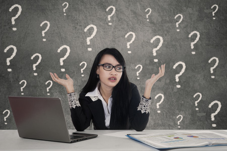 Pretty female entrepreneur working on the table and looks confused with question marks on the background photo