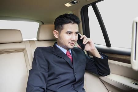 detras de: Joven empresario vistiendo traje formal y sentado en el asiento de atrás mientras se habla por el teléfono en el coche