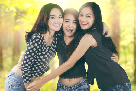 students group: Portrait of beautiful teenage girls enjoying summer holiday in the nature and embrace each other Stock Photo