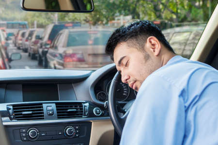 Tired young businessman driving a car and take a rest in the traffic jam
