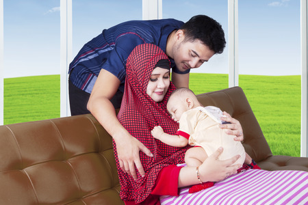 muslim baby: Two young muslim parents giving a care of their baby boy on the sofa at home