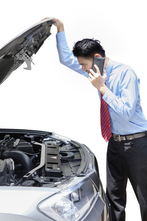 car trouble: Young man calling for help while looking at the broken car machine