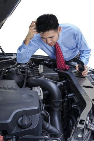 car mechanic: Young entrepreneur looks confused to repair the machine of broken car Stock Photo