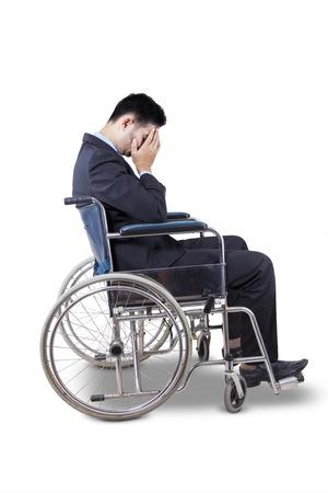 sillon: Joven empresario vistiendo traje formal y se ve triste, sentado en la silla de ruedas, aislado en blanco