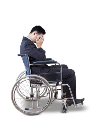 Young businessman wearing formal suit and looks sad, sitting in the wheelchair, isolated on white photo