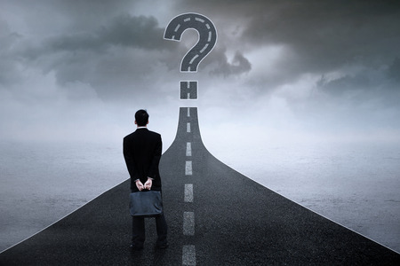 Back view of male entrepreneur standing on the highway while looking at the question sign photo