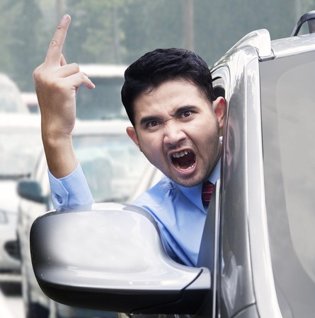 middle finger: Portrait of furious businessman showing a middle finger while driving a car on the road