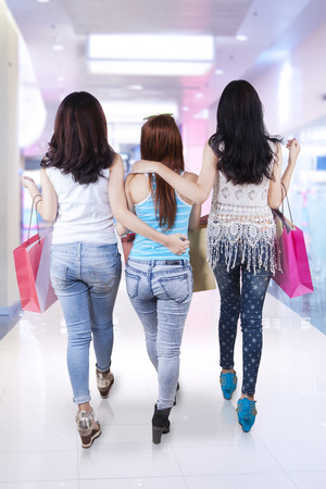 Rear view of teenage girls walking in the shopping center together while carrying shopping bags photo