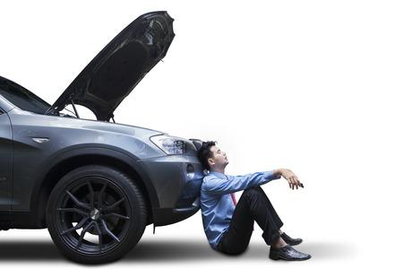 Fatigué jeune homme qui attend une aide alors qu'il était assis près de la voiture cassée, isolé sur blanc