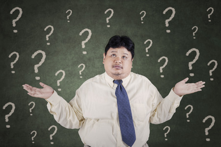 fat concept: Portrait of overweight businessman looks confused with question marks on the blackboard
