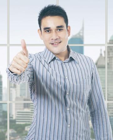 hombres trabajando: Empresario de sexo masculino de pie cerca de la ventana en la oficina y que muestra el pulgar hacia arriba