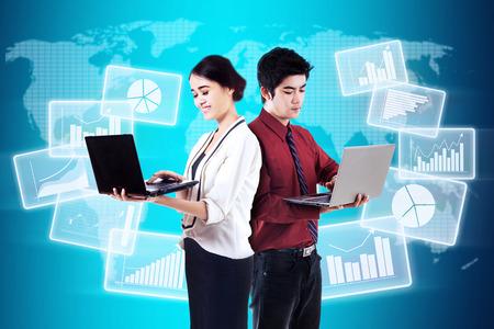 jovenes empresarios: Dos empresarios jóvenes que trabajan con ordenador portátil y futuristas estadísticas de las empresas globales Foto de archivo