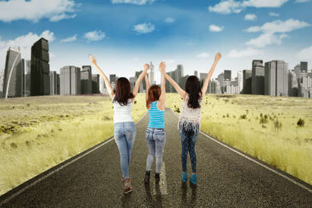 highway love: Back view of three teenage girls raised hands together on the highway Stock Photo