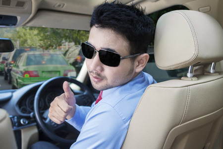 riches adult: Young man driving a car while showing thumb up on the camera, shot on the road Stock Photo