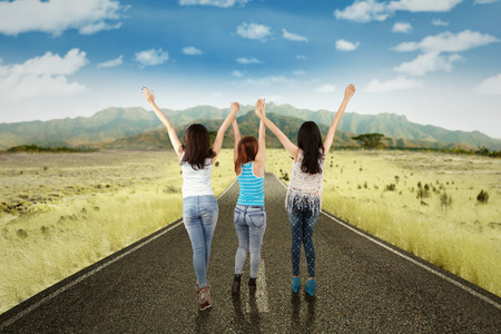 highway 3: Rear view of three teenage girls walking on the countryside road and raised hands together