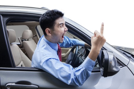Young man driving a car and looks angry, screaming and showing middle finger Stock Photo