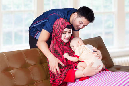 muslim baby: Portrait of muslim parents with their baby boy, sitting on sofa in the living room at home