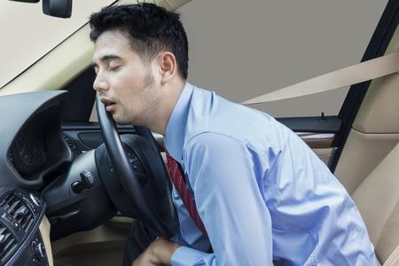 運転車と見える青年実業家疲れて、安全ベルトを着用しながら車の中で寝ています。