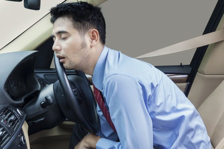 cinturon seguridad: Hombre de negocios joven que conduce un coche y se ve cansado, durmiendo en el coche mientras llevaba el cinturón de seguridad