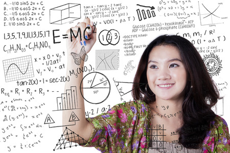 Smart female high school student writing various high school math and science formula