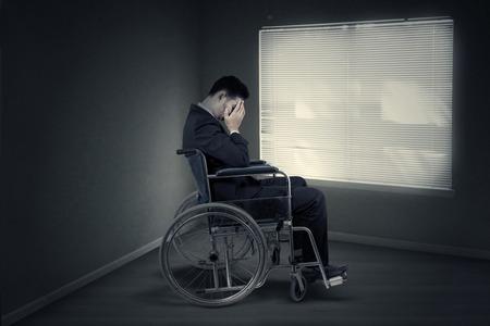 homme triste: Portrait d'entrepreneur handicapée a l'air triste et assis dans fauteuil près de la fenêtre