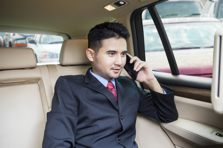 back seat: Young businessman sitting on the back seat in the car while talking on the phone