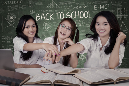joining hands: Attractive female high school students joining hands together in the classroom Stock Photo