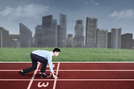Young entrepreneur in ready position to run and compete for success photo