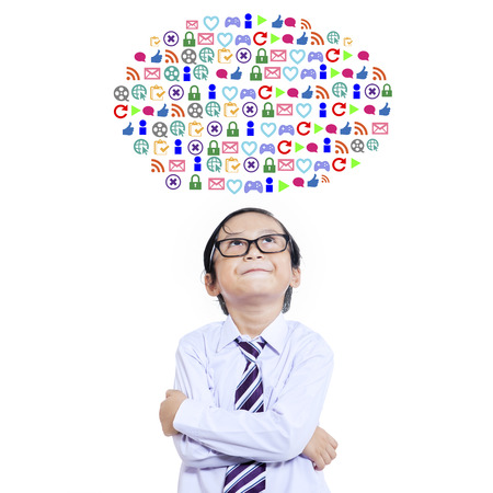 business like: Cute little boy standing in the studio while imagine web icons, isolated on white background