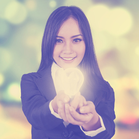 lamp light: Young businesswoman showing bright light bulb on the camera, shot with bokeh background Stock Photo