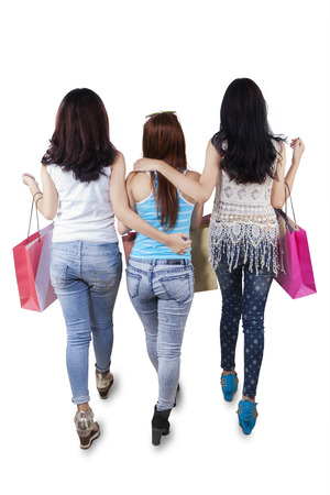 Back view of teenage girls walking in the studio while carrying shopping bags, isolated on white photo