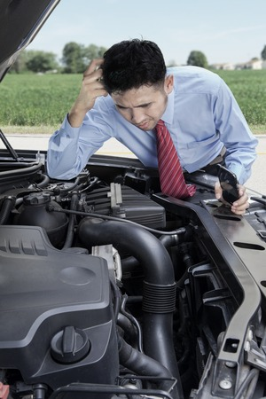 Portrait of young man looks worried while looking at his broken car machine photo