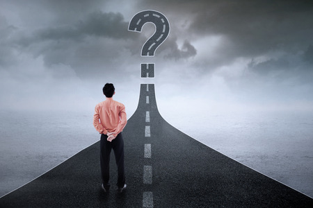 Rear view of young businessman standing on the road while looking at question sign